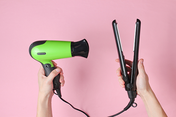 Hair care. Female hands holding hair straightener and hairdryer on pink background. Top view